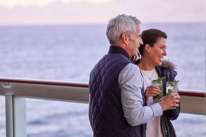 Una pareja disfrutando de bebidas frente al mar